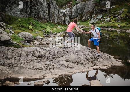 Escursionismo coppia sulle rocce, cane montagna, BC, Canada Immagini Stock