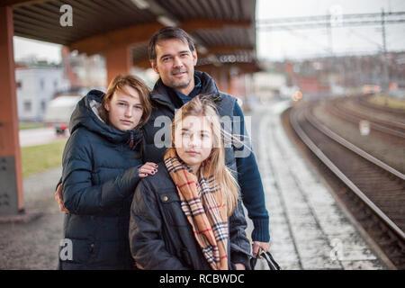 Padre con le figlie a stazione ferroviaria Immagini Stock