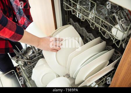 La donna prende piatti puliti dalla lavastoviglie. Immagini Stock