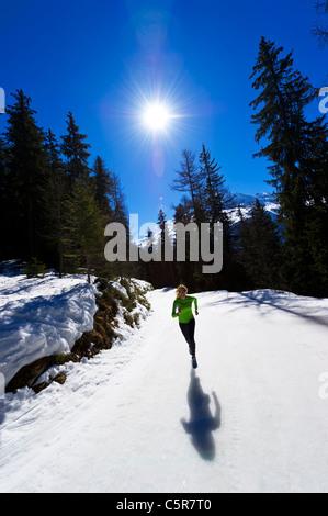 Una ragazza jogging in alta quota in montagna innevata. Immagini Stock
