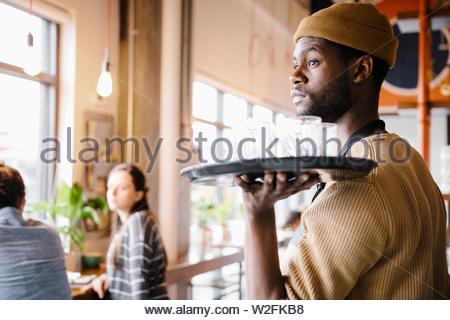Cameriere con vassoio di bicchieri in ristorante Immagini Stock