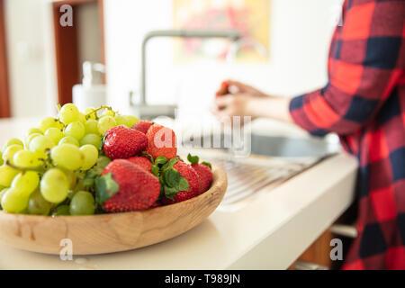 Ciotola di legno con uva verde e fragole in cucina e una donna risciacqui frutti sullo sfondo. Immagini Stock