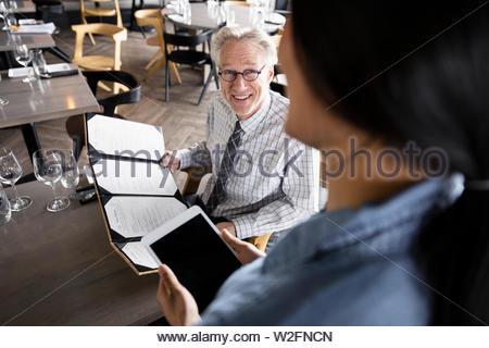 Cameriera con tavoletta digitale prendendo ordine dalla sorridente imprenditore senior presso il ristorante la tabella Immagini Stock