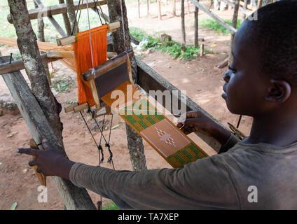 L'uomo africano dalla tribù Baoulé tessitura in un tradizionale fabbrica tessile, Région des Lacs, Bomizanbo, Costa d'Avorio Immagini Stock