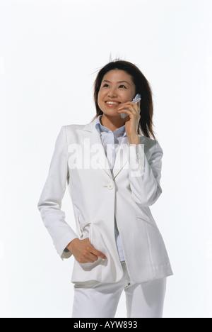 La donna in bianco suite a parlare su un telefono cellulare Immagini Stock