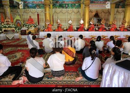 Seduti i monaci buddisti pregano in ricordo del defunto, Wat Ongs Teu Mahawihan (il Tempio del Buddha di pesanti), Vientiane, Laos, Indocina, Southeas Immagini Stock