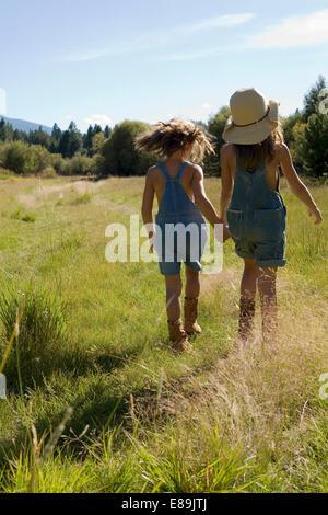 Sorelle in tute di camminare nel campo Immagini Stock