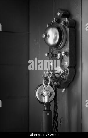 Vecchio telefono antico appeso alla parete. La tecnologia vintage. Classic apparecchiature di comunicazione. Immagini Stock