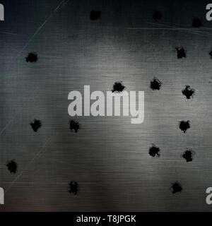 Fori di proiettile in un graffiato la superficie metallica Immagini Stock