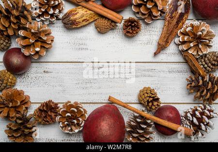 Le decorazioni di Natale su un bianco sullo sfondo di legno con copia spazio. Pigne, garland, bacche e rami di pino Immagini Stock