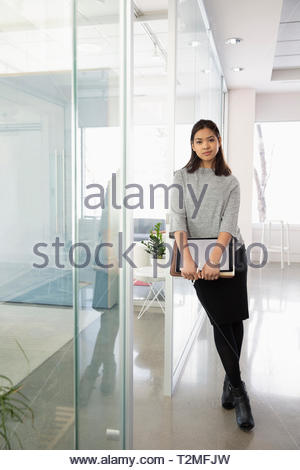 Ritratto fiducioso imprenditrice in ufficio moderno Immagini Stock