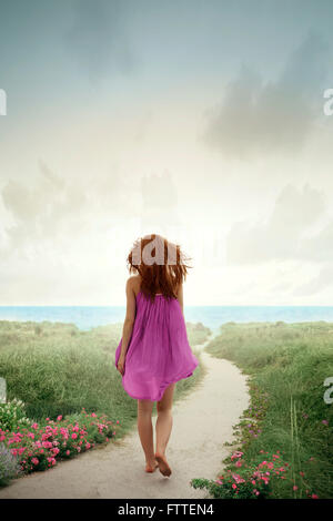 Donna che cammina sulla spiaggia fiorita Immagini Stock