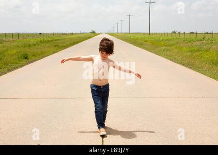 Ragazzo camminando lungo il marciapiede Immagini Stock