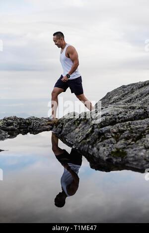 L'uomo escursionismo sulle rocce Immagini Stock