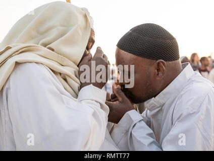 Gli uomini di baciare le mani durante il venerdì celebrazione sufi al Sheikh Hamad el Nil tomba, Stato di Khartoum, Omdurman, Sudan Immagini Stock