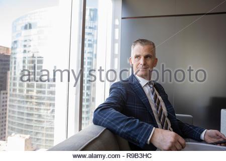 Imprenditore fiducioso guardando fuori ufficio urbano finestra Immagini Stock