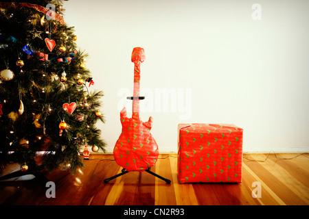 Chitarra e amplificatore regali di Natale con l'albero. Immagini Stock