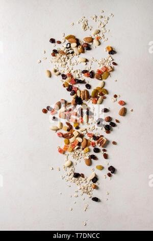 Varietà di frutta secca, noci e fiocchi di avena per cucinare in casa sana colazione muesli muesli o barrette energetiche su bianco sullo sfondo di texture. Appartamento Immagini Stock