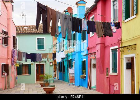 Le linee di abbigliamento in un tradizionale cortile multicolore, Burano, Venezia, Veneto, Italia Immagini Stock