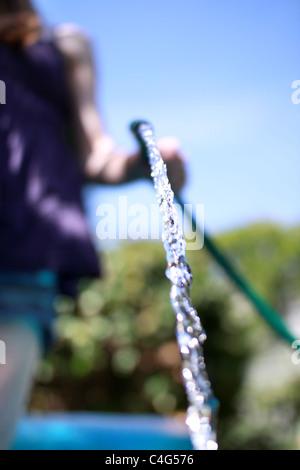 Ragazza con un tubo flessibile Immagini Stock