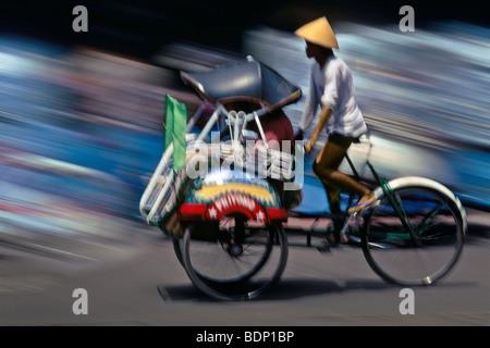 Becak (riscio' bicicletta taxi) in movimento sfocate, Yogyakarta, Java, Indonesia Immagini Stock