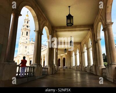 Una donna orologi il campanile della sactuary di Nostra Signora del Rosario da arcate del santuario di Fatima, Portogallo Immagini Stock