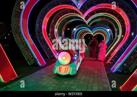 Un giocattolo treno passa attraverso una illuminata a forma di cuore in tunnel Tsvetochny o fiore parco nel centro di Grozny capitale della Cecenia ufficialmente la Repubblica cecena nel Nord Caucaso Distretto federale della Russia. Immagini Stock