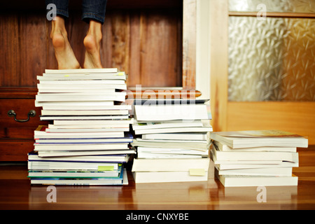 Ragazza sorge punta di piedi sulla pila di libri Immagini Stock