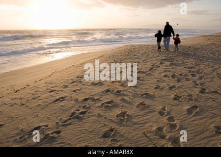 Una famiglia di camminare sulla spiaggia Immagini Stock