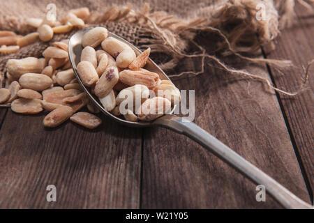 Arachidi tostate su un vecchio cucchiaio e composizione dal vecchio legno e materiale. Immagini Stock