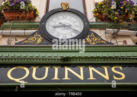 Irlanda del Nord, Co Down, Newcastle, Main Street, clock di Guinness al di sopra di Quinns Bar segno dorato Immagini Stock
