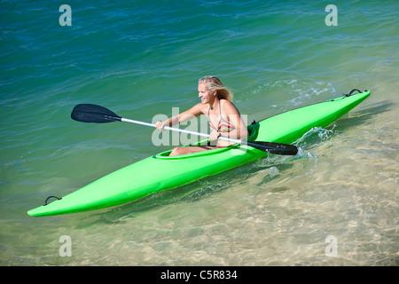 Una donna pagaie la sua canoa in una giornata di sole. Immagini Stock