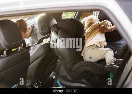 Madre tenendo fuori figlio (18-23 mesi) al di fuori della vettura Immagini Stock