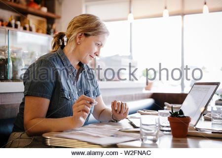Focalizzato la donna lavora al computer portatile in cafe Immagini Stock