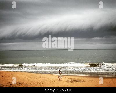 Una giovane donna corre in una spiaggia di Chipiona, Cadice, Andalusia, Spagna Immagini Stock