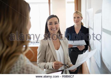 Donna sorridente architetti rivedendo blueprint in office meeting Immagini Stock