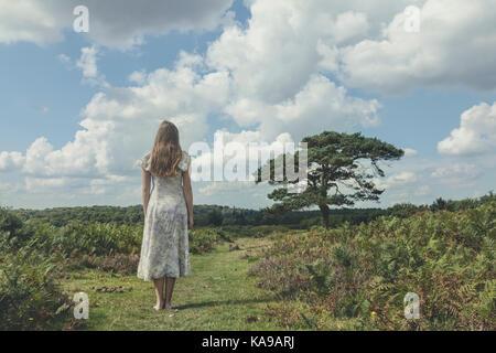 Una ragazza in un abito floreale è staning su un campo con bracken Immagini Stock