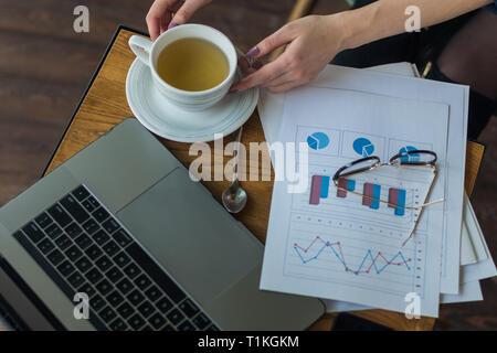 Area di lavoro con computer portatile, ragazza con le mani in mano, notebook, taccuino. Vista superiore tabella office desk. Freelance di posto di lavoro Immagini Stock