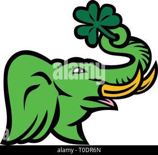 Icona di stile retrò illustrazione di elefante verde con grande zanna tenendo un gigante shamrock irlandese utilizzando è tronco visto dal lato su sfondo isolato. Immagini Stock