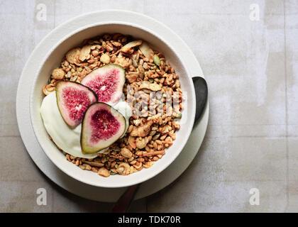 Una ciotola di muesli servita con vaniglia yogurt e fette di figg. Immagini Stock