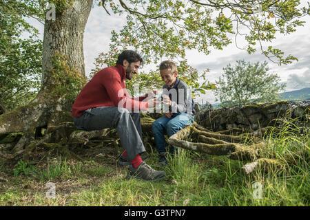 Un uomo che mostra il suo Figlio come utilizzare una fotocamera sulla riva del lago Bala in Galles. Immagini Stock