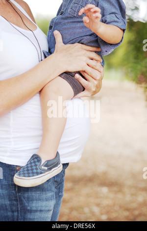 Gravidanza mamma azienda giovane ragazzo sul baby bump Immagini Stock