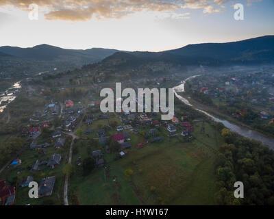 Riprese aeree sopra il villaggio di mykulychyn nella regione dei Carpazi dell'Ucraina occidentale come il sole Immagini Stock