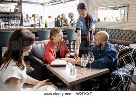 Cameriera di servire la gente di affari in ristorante Immagini Stock