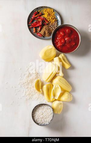 Gli ingredienti per cucinare vegan curry. Raw maturo pelato jackfruit con il bianco riso crudo, tagliate a pezzetti i pomodori e spezie in ceramica bocce su bianco marbl Immagini Stock