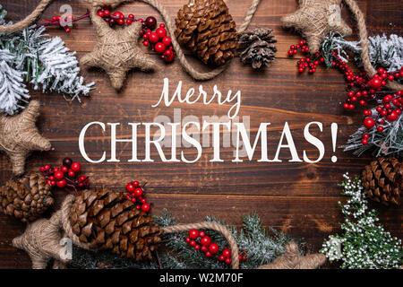 Le decorazioni di Natale su di un legno marrone sfondo con copia spazio. Pigne, garland, bacche e rami di pino Immagini Stock
