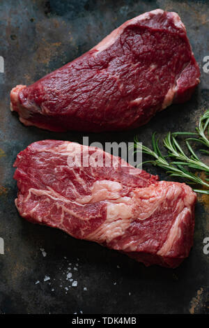 Materie black angus ottima bistecca di manzo varietà con rosmarino, sale marino e spezie Immagini Stock