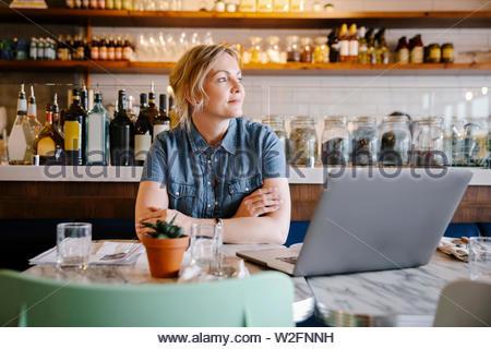 Cafe femmina proprietario lavora al computer portatile in cafe Immagini Stock