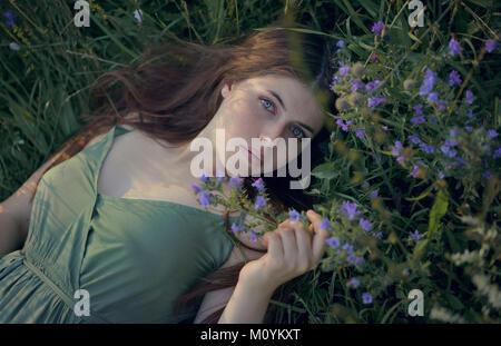 La donna caucasica posa in erba con fiori di campo Immagini Stock