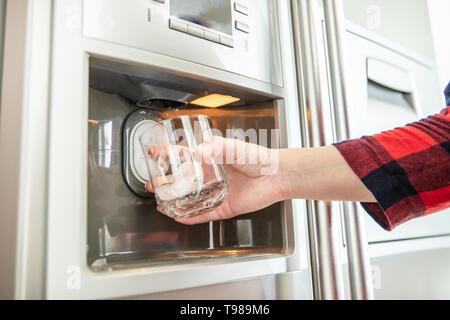Donna di mano trattiene il vetro e utilizza il frigorifero per rendere fresche e pulite di cubetti di ghiaccio. Immagini Stock